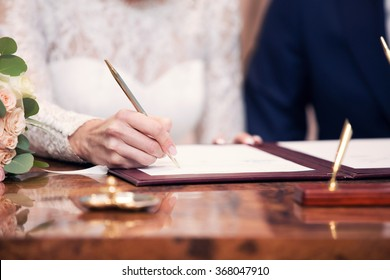 newlyweds append signatures in a registry office during wedding registration