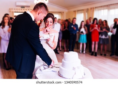 newlyweds is cutting their wedding cake. The bride is eating a wedding cake. guests in the restaurant hall
