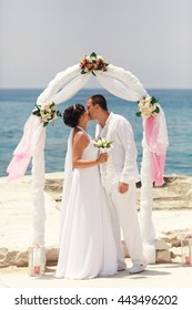 Newlyweds dressed in white kiss under a wedding altar standing by the sea