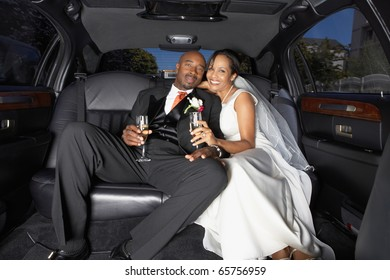 Newlyweds drinking champagne in their limo