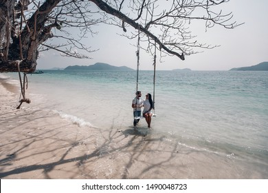Newlyweds enjoying each other on the secret beach in one of the Thai bays, both are dressed in white, lady sits on rope swings; paradise concept.