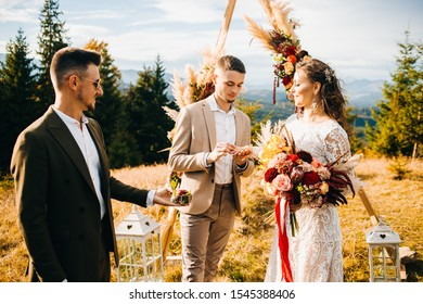 Newlyweds exchange rings during their beautiful wedding ceremony outdoors. Wedding ceremony in rustic style.