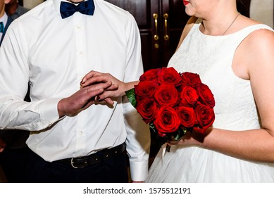 Newlyweds exchange rings in the registry office during the registration of the wedding.