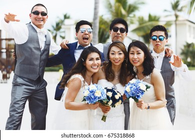 Newlyweds and firends have fun posing outside