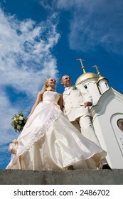 Newlyweds in front of church.
