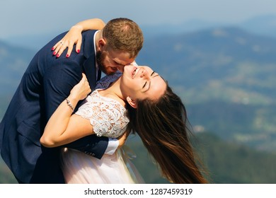 Newlyweds have fun at the top of the mountain. the bride has bend back and smiles and the wind blowing on her hair. the groom embraces the bride behind the waist