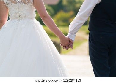 newlyweds hold hands