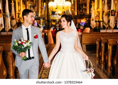 the newlyweds hold hands and leave the church after the ceremony