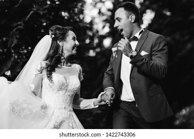 the newlyweds hold hands and look at each other on black and white photography