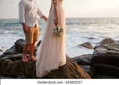 The newlyweds hold hands at the wedding on the beach. Couple holding hands, ocean background
