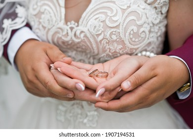 Newlyweds hold wedding rings in their hands.
