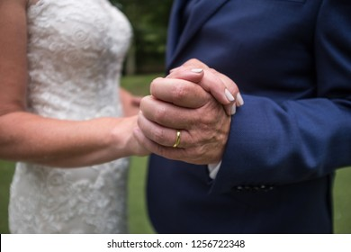 newlyweds holding hands after getting hitched, with their new rings