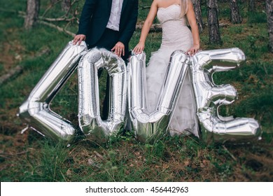 newlyweds holding love letter balloons