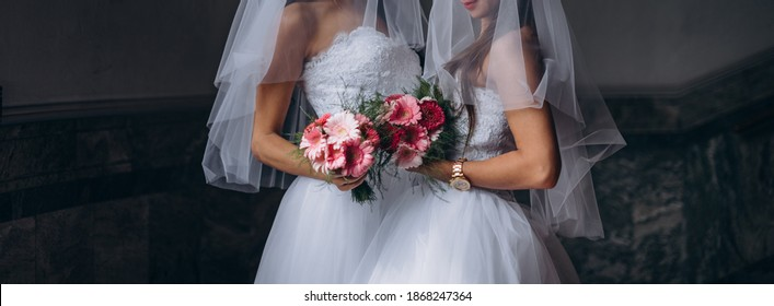 Newlyweds lesbian couple on their happy wedding day wearing white dresses and holding bouquets. Equality concept.