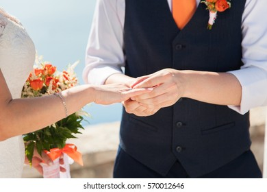 Newlyweds marry at a wedding ceremony. The bride holds wedding bouquet from orange roses, she is dressed in white lace wedding dress. The groom is wearing in white shirt, orange tie and blue vest.