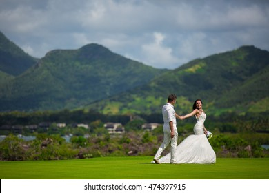 The newlyweds are on the golf course. Bird eye view. Aerial view. Mauritius island. drone fly. Mountains. Virgin place. Just married relaxing. Wedding on the golf course