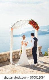Newlyweds on wedding ceremony above sea and mountains. Bride holds wedding bouquet from orange roses, she is dressed in white wedding dress. The groom is wearing in shirt, orange tie and blue vest.