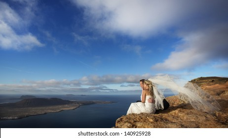 Newlyweds sitting on the edge of a precipice and looking at the ocean in Canary Islands.