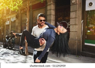 Newlyweds spend their honeymoon and have fun on the streets of a Spanish town. Handsome young bearded husband holding in his arms his fascinating wife. Happy couple enjoying a sunny and romantic day