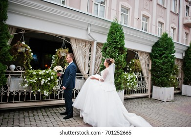 Newlyweds walking on the street of an old town with cafe and flowers on it on a wedding day.