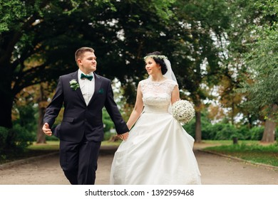 newlyweds are walking in the park and looking at each other. The bride is holding a wedding bouquet