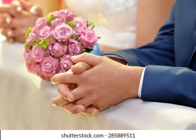 Newlyweds with wedding rose bouquet at the church