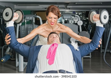 Newlyweds working hard. Gym used to illustrate the concept