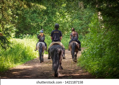 Newmarket, Cambridgeshire, UK - Circ June 2019: Trio of young people seen riding horses and a pony through dense woodland in early summer. Part of a riding hack from nearby stables.