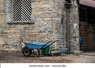 Newmarket, Cambridgeshire, UK - Circa June 2019: Detailed view outside a stable and livery block showing various tools used to clean out the horse stables. The building is a Grade 2 listed stone house