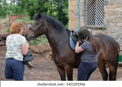 Newmarket, Cambridgeshire, UK - Circa June 2019: Young female student seen preparing to ride a New Forest pony at a livery yard. The owner can be seen hold his reigns prior to the girl saddling up.