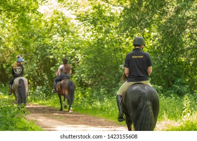 Newmarket, Cambridgeshire, UK - Circa June 2019: Trio of young students, the nearer one in focus seen enjoying a horse ride through a designated wildlife area. The young man is wearing a polo shirt.