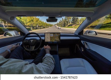 Newport Beach, CA / USA - 10/24/2019: Interior view of autonomous Tesla car in full self driving autopilot mode showing the advanced innovation of future electric cars.