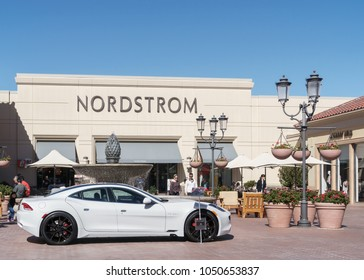 Newport Beach, CA, USA - February 19, 2018: A white 2018 Karma Revero electric sports car sits in front of Nordstrom department store in Fashion Island shopping center.