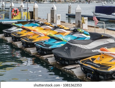 Newport Beach, CA, USA - January 29, 2018: Row of colorful sea-do jet skis for rent at wooden dock. These vehicles are popular fun personal watercraft.