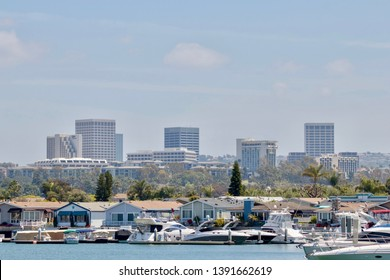 Newport Beach, CA / USA - May 5, 2019: boats docked in a marina by houses with high rise buildings in the background in Newport Beach California
