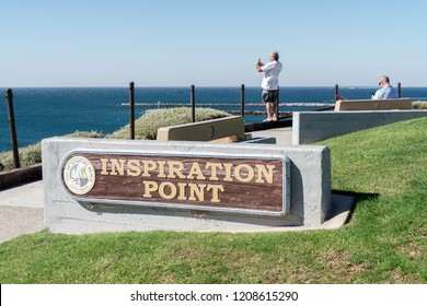 Newport Beach, CA, USA - October 15, 2018: Sign to Inspiration Point cliff lookout.  Scenic tourist spot with view of the ocean. People relaxing in background. Blue sky.
