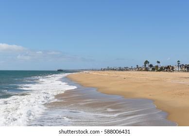 NEWPORT BEACH, CALIFORNIA - FEBRUARY 22, 2017: Balboa Peninsula and Pier. Homes line the beach along the Southern California coastline, viewed from the Newport jetty.