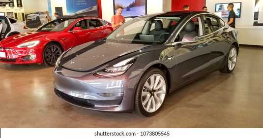 Newport Beach, California / United States of America - April 18 2018: Midnight Silver Metallic Tesla Model 3 and Signature Red Model S Displayed At the Fashion Island Showroom.