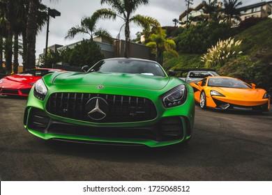 Newport Beach, California. Year 2018: Front view of three supercars. green Mercedes-AMG GTR, red Lamborghini Huracan, orange McLaren. Beautiful Machines.
