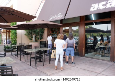 Newport Beach, California/United States - 07/30/2019: People stand in line outside the door of the dessert shop known as Sprinkles Cupcakes