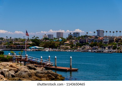 Newport Beach skyline from Balboa Island. Mansions on shoreline with the large office buildings and thunder clouds and palm trees in the background.