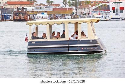 NEWPORT BEACH/CALIFORNIA - MAY 21, 2017: Folks enjoying a ride on a Duffy cruising through Newport Beach harbor. Viewed from Balboa Island. Newport Beach, California USA
