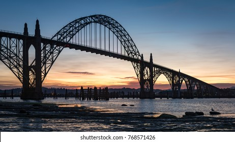 Newport bridge in Oregon during an early morning sunrise with the bridge in silhouette.
