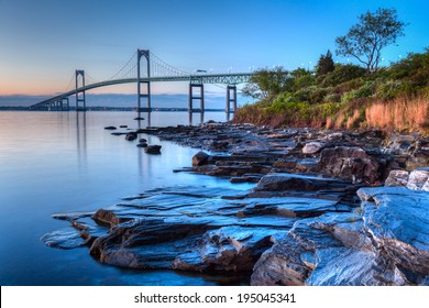 Newport Bridge Sunrise / This is a long exposure HDR of the illuminated Newport bridge from Taylor's Point near Jamestown, Rhode Island, USA. Taken at sunrise with rocky seascape in foreground.