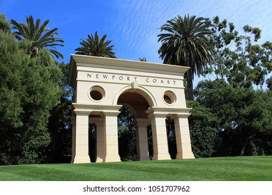 Newport Coast arch structure against greenery and blue sky