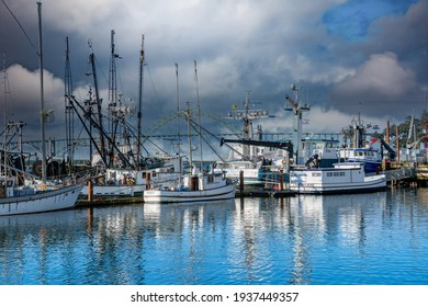 Newport, Oregon - 3-9-2021: Commercial fishing boats in harbor with Yaquina Bay Bridge and stormclouds in background