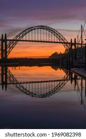 Newport Oregon Bridge and Marina with colorful sunset sky and water reflection.