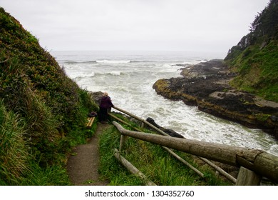 NEWPORT, OREGON - MAY 23, 2018 - Visitor looks down to ocean waves channeled into narrow gorge of Devil's Churn at  Cape Perpetua, Oregon