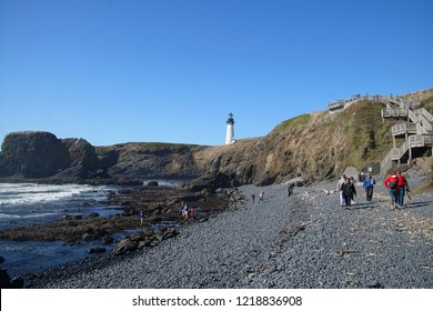 NEWPORT, OREGON - OCT 4, 2018 - Families explore the tide pools of Cobble Beach below Yaquina Head lighthouse in Newport, Oregon