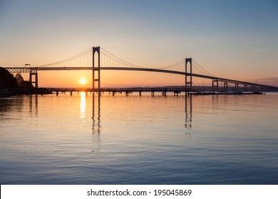 Newport Rhode Island Bridge Sunrise / Morning blue and orange sunrise under the Newport Pell Bridge seen from Jamestown, Rhode Island, USA.
